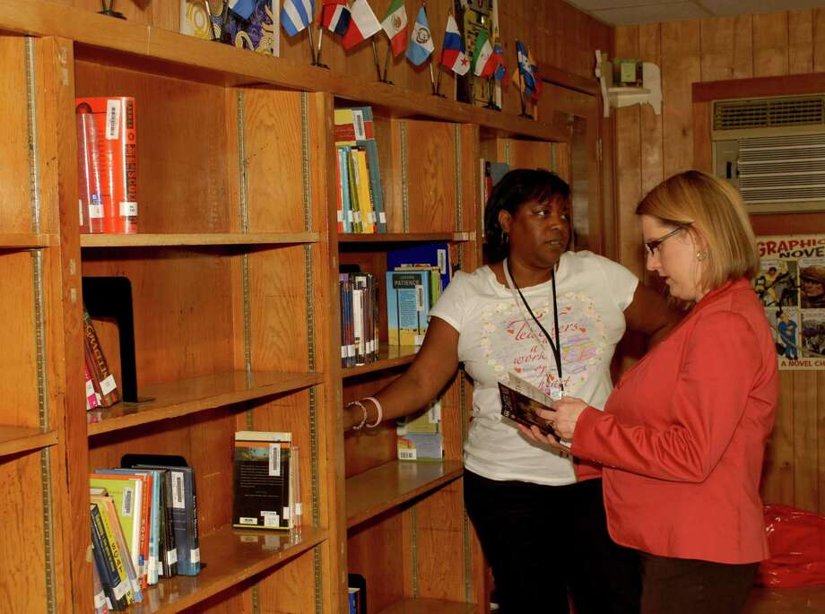 Wharton Dual Language Academy Librarian Karen Hogg, left, and Principal Jennifer Day look at the library's books, which are housed in one of the school's temporary buildings. The school would get a new library if the Houston school district bond proposal is approved next month. Photo: George Wong / Freelance