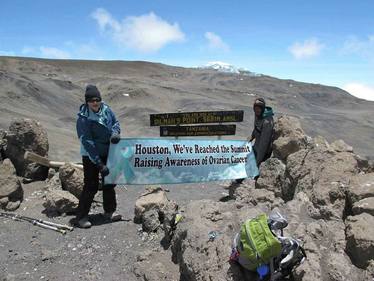 A group organized by Heights resident Shana Ross dared climb a peak of Mount Kilimanjaro as a way for each member to promote ovarian cancer awareness and prove they could face some seemingly insurmountable challenges. Heights resident Becky Pope, above left, and a guide proudly display the group's banner. One of the emotional moments was when they viewed sunrise from the summit of a peak on what is considered the heighest walkable mountain in the world.