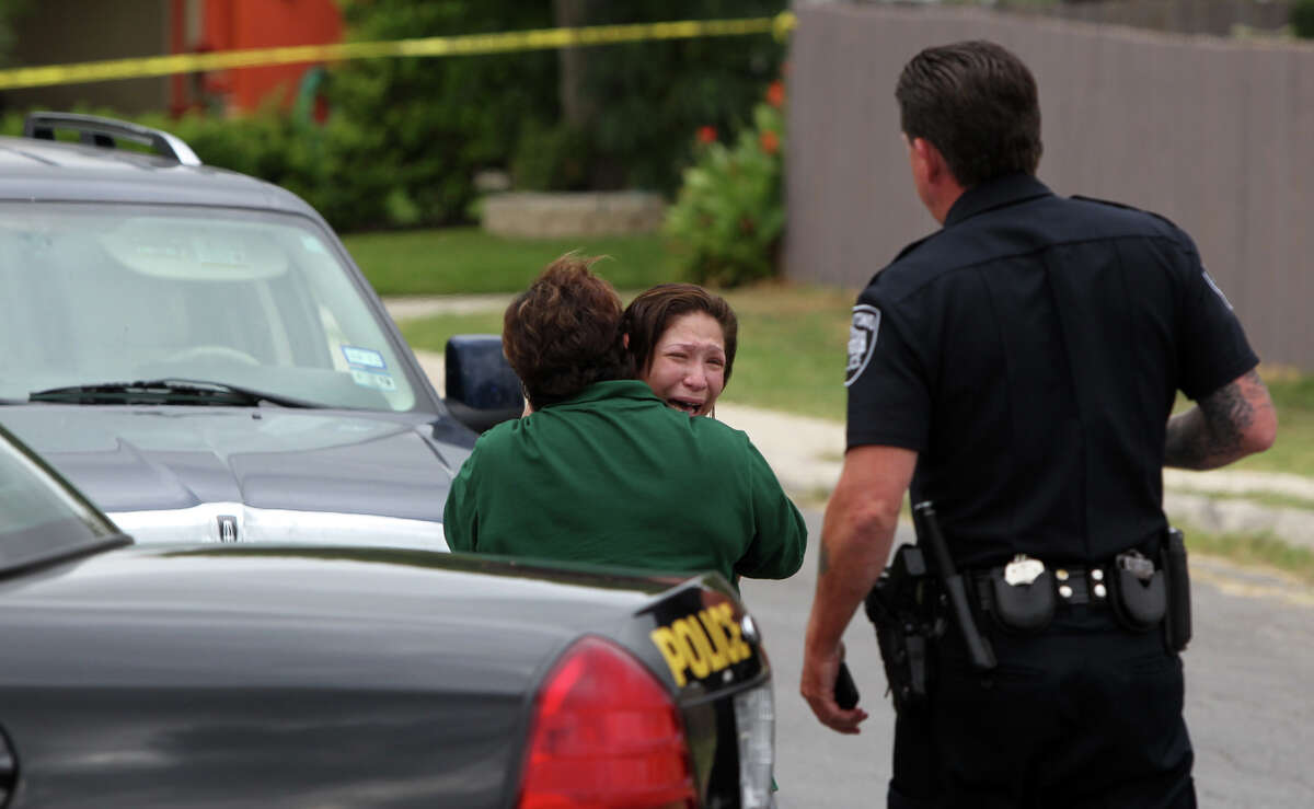 A woman (facing) that police identified as the wife of a shooting victim grieves at the intersection of Old Sky Harbor and Port of Call where a man who had been shot was found about 10:00 a.m. Tuesday October 23, 2012. The shooting victim was taken by Air Life to University Hospital in undetermined condition. The suspect in the shooting remains at large.