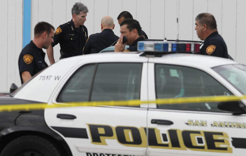 San Antonio police investigate the scene where the body of a 57-year-old man was found behind a barber shop on the 300 block of Valley Hi Drive. Police Chief William McManus (second from left) said a passerby came across the body in the 300 block of Valley Hi Drive around 9:15 a.m. He had been stabbed and cut throughout his torso, he said, adding it appeared the man had been killed overnight.