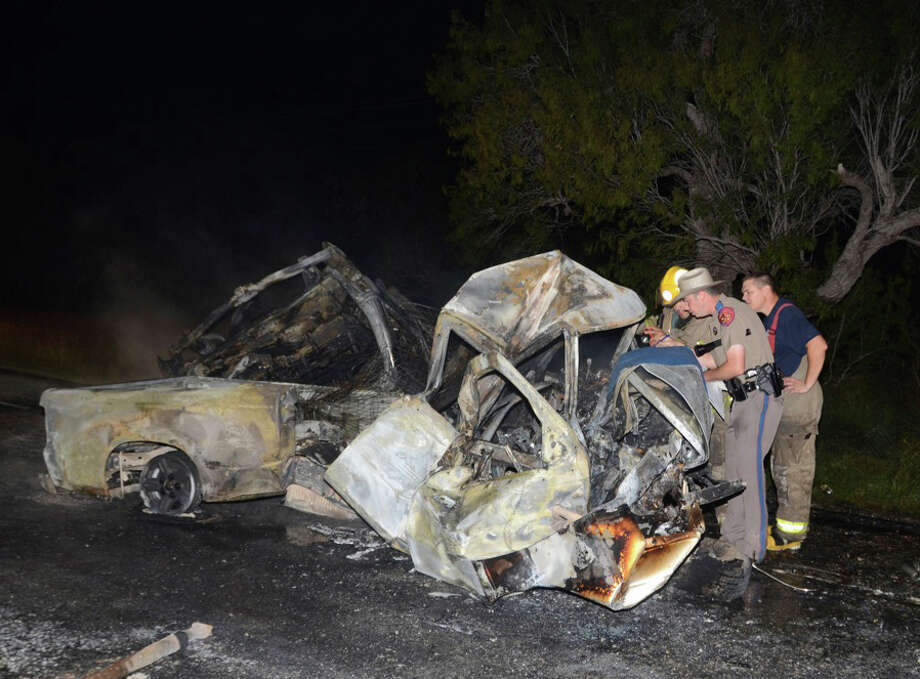 The charred remains of a two vehicles involved  in a fatal crash smolder on the roadway in Atascosa County early Sunday morning.  Officials are still trying to identify a man who was killed in a fiery crash over the weekend. The victim, a 61-year-old man from Laredo, was pronounced dead at the scene of the crash, which occurred on Texas. The deceased man was trapped in his pickup. A 31-year-old man in the other vehicle was badly burned and was flown to San Antonio Military Medical Center with critical injuries. Photo: Xavier Garica/Special To San Ant