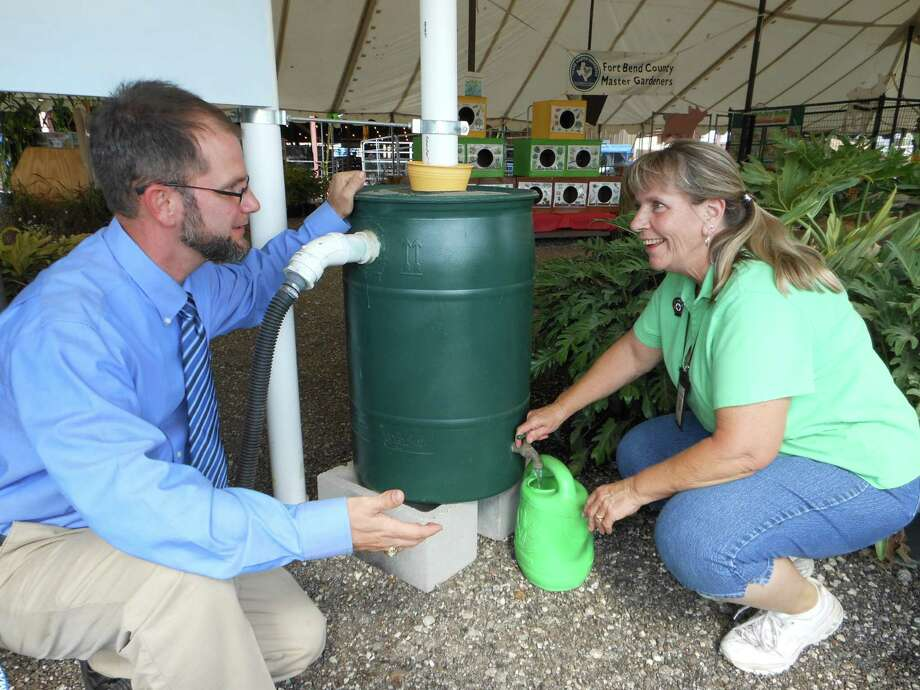 "Extension agents show people how to put new concepts in action: Here, Fort Bend County Extension Agent Boone Holladay and Margo ""Mac"" McDowell get water out of a rain barrel at the Fort Bend County Fair."