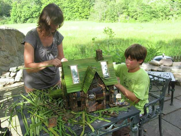 "Lori Lenz and her son Edward of Deep River, Conn., work on their contribution to the Museum's Wee Faerie Village, which runs through Monday, Nov. 5, 2012. ""Marsh Light Manor,"" a dwelling for the faeries of light, incorporates natural elements that they collected during the summer. Lori Lenz is an art teacher at Chester (Conn.) Elementary School. The outdoor exhibition, which features structures from more than 30 artists, features special weekend programming, as well. For more information, and a schedule of events, visit FlorenceGriswoldMuseum.org or call 860-434-5542. Photo: Contributed Photo"
