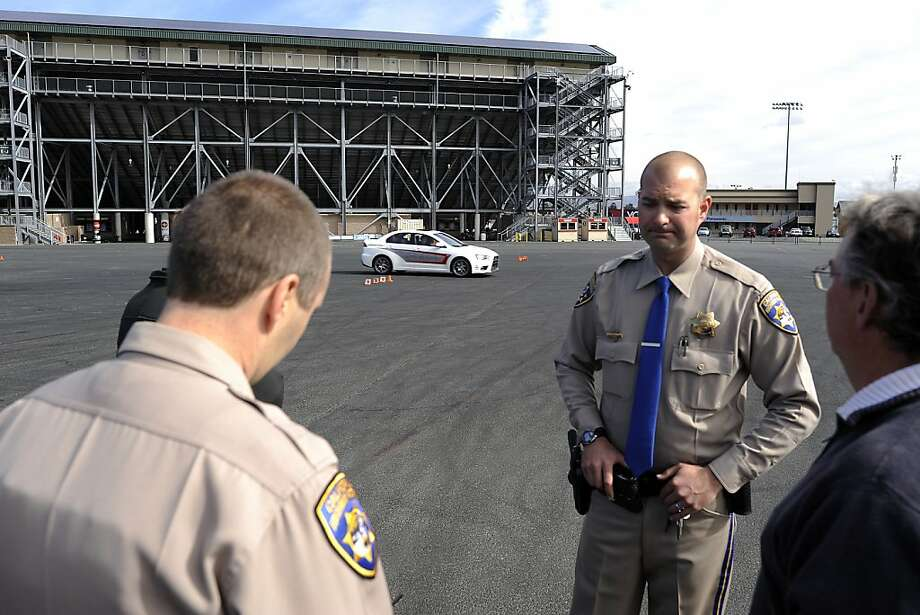 "Officer Garrett Ray (right) of the California Highway Patrol's Napa office stands by with other officers and members of the media as a student and instructor try the ""lane change test."" Photo: Michael Short, Special To The Chronicle"