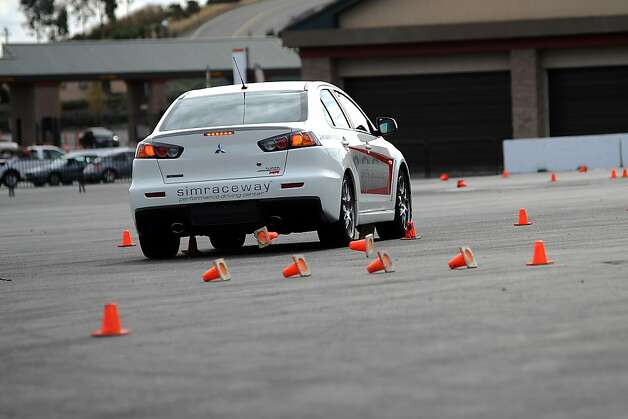 "Cones fly, deducting points,  as a student driver runs through them during the ""lane change test"".  Sonoma Raceway hosted an event in which teenage drivers are run through various distractions like texting, opening a bottle of water, changing the radio station, etc., so they can see how it can effect their driving.  Sonoma, CA, Tuesday October 23rd, 2012 Photo: Michael Short, Special To The Chronicle"