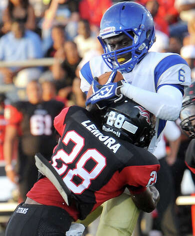 Ozen's Deandre Burrell is brought down by Memorial's Darius Lemora at Memorial Stadium in Port Arthur, Friday. Tammy McKinley/The Enterprise Photo: TAMMY MCKINLEY
