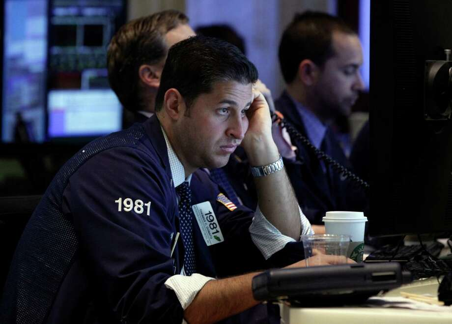 Trader Thomas Donato looks at a screen as he works on the floor of the New York Stock Exchange Tuesday, Oct. 23, 2012. Stocks are falling sharply at the opening of trading on Wall Street after 3M and DuPont slashed their earnings forecasts. (AP Photo/Richard Drew) Photo: Richard Drew / AP