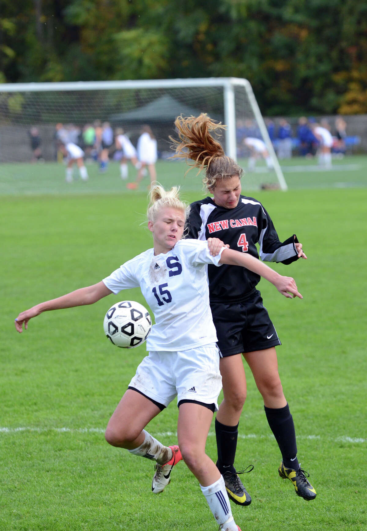 New Canaan's Marina Braccio (4) challenges Staples' Ryan Kirshner (15) for the ball during the girls soccer game at Loeffler Field at Staples High School in Westport on Tuesday, Oct. 23, 2012.