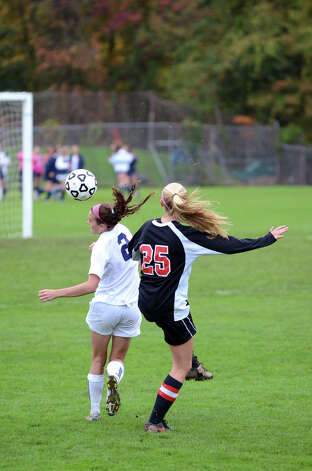 Staples' Olivia Gerrard (2) heads the ball as New Canaan's Kelly Armstrong (25) defends during the girls soccer game at Loeffler Field at Staples High School in Westport on Tuesday, Oct. 23, 2012. Photo: Amy Mortensen / Connecticut Post Freelance