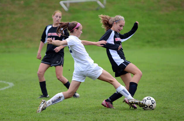 Staples' Olivia Gerrard (2) attempts to tackle the ball from New Canaan's Abigail Farley (11) during the girls soccer game at Loeffler Field at Staples High School in Westport on Tuesday, Oct. 23, 2012. Photo: Amy Mortensen / Connecticut Post Freelance