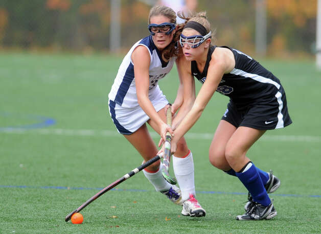 Staples' Shelby Phares and Darien's Katie Shanahan battle for the ball during their field hockey game at Staples High School in Westport. Photo: Autumn Driscoll / Connecticut Post