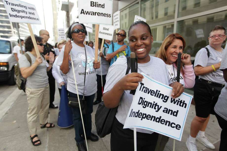"Latreace McCoy, 29, of Bryan Station, participates in the ""White Cane Safety Day"" march as they are headed towards City Hall to bring awareness to blindness on Tuesday, Oct. 23, 2012, in Houston. Photo: Mayra Beltran, Houston Chronicle / © 2012 Houston Chronicle"