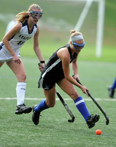 Darien's Kat Huber controls the ball as Staples' Elizabeth Bennewitz moves in to defend during their field hockey game at Staples High School in Westport. Photo: Autumn Driscoll / Connecticut Post
