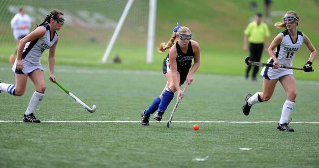 Darien's Sloane Bessey controls the ball as Staples' Jackie Lawrence, left, and Elizabeth Bennewitz move in to defend during their field hockey game at Staples High School in Westport. Photo: Autumn Driscoll / Connecticut Post
