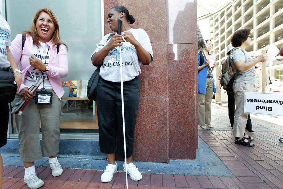 "Lucy Aldrete, 57, and Latreace McCoy, 29, of Bryan Station, stand in line to begin the ""White Cane Safety Day"" march to bring awareness to blindness as the City of Houston continues to observe Disability Awareness Month. Photo: Mayra Beltran, Houston Chronicle / © 2012 Houston Chronicle"