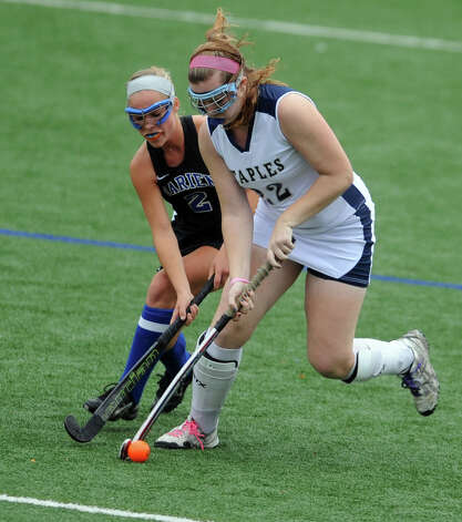Darien's Kat Huber and Staples' Audrey Reedy battle for the ball during their field hockey game at Staples High School in Westport. Photo: Autumn Driscoll / Connecticut Post