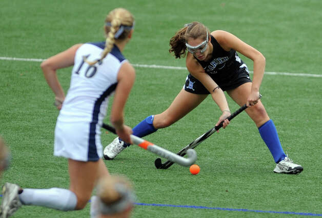 Darien's Maggie Wells passes the ball as Staples' Jenna McNicholas moves in to defend during their field hockey game at Staples High School in Westport. Photo: Autumn Driscoll / Connecticut Post