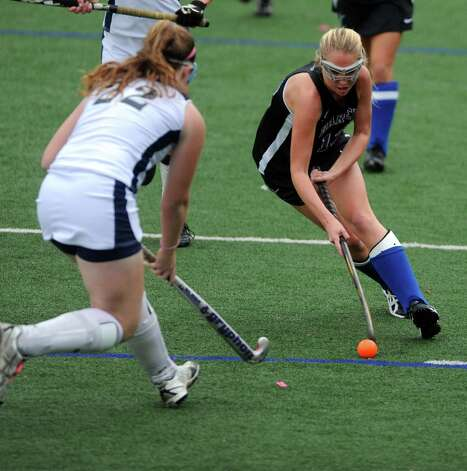 Darien's Claire Culliton controls the ball as Staples' Shannon Connors defends during their field hockey game at Staples High School in Westport. Photo: Autumn Driscoll / Connecticut Post