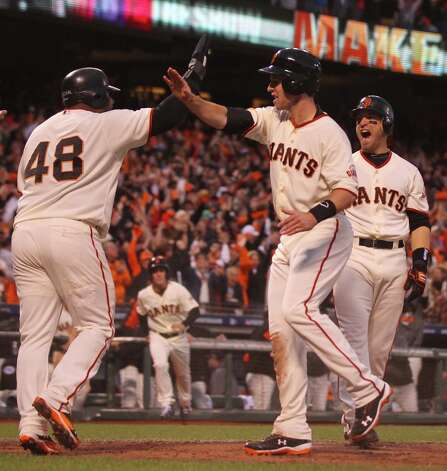 Giants' third baseman Pablo Sandoval celebrates with Buster Posey and Marco Scutaro after the 3 scored in the 3rd inning during game 7 of the NLCS at AT&T Park on Monday, Oct. 22, 2012 in San Francisco, Calif. Photo: Lance Iversen, The Chronicle / ONLINE_YES