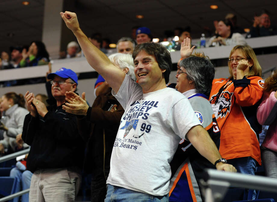 A fan celebrates a goal by Sound Tigers Brandon DeFazio gets the puck past Providence's goalie Michael Hutchinso, during home opener hockey action against Providence at the Webster Bank Arena in Bridgeport, Conn. on Friday October 13, 2012. Photo: Christian Abraham / Connecticut Post