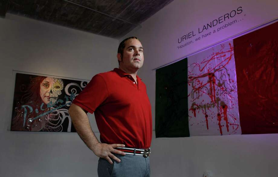 "James Perez, owner of Cueto James Art Gallery, poses between pieces titled ""Ego"", left, and ""Legalize Drugs"", right, that will be in the show titled ""Uriel Landeros: Houston We Have a Problem"" shown Tuesday, Oct. 23, 2012, in Houston. Uriel Landeros is the man accused of vandalizing a Picasso painting at the Menil with spray paint in June. Photo: Melissa Phillip, Houston Chronicle / © 2012 Houston Chronicle"