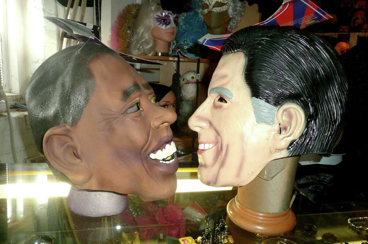"""Smiling their way to Election Day are these Halloween masks of the two presidential candidates, President Barack Obama and former Governor Mitt Romney. Sales of the masks, which can be found at Sophia's Costumes in Greenwich, indicate a close race for the Oval Office. """"My sales have been 50-50,"""" says store owner Sophia Scarpelli."""