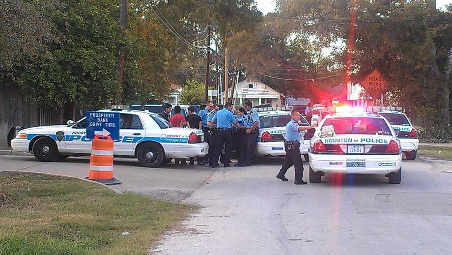 Officers survey the scene of the suspected stash house on Tuesday.