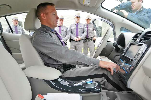 State Trooper Brett Yorgey of Troop D, sits in a 2012 Nissan Leaf electric car at the State Police Academy, where more than 40 state police collision investigators received safety training for those responding to accidents involving electric and electric-hybrid vehicles,   on Tuesday Oct. 23, 2012 in Albany, NY.  State Police officials quoted estimates that up to 1.5 million of the vehicles  could be on the road by 2015.  (Philip Kamrass /  Times Union) Photo: Philip Kamrass / 00019790A