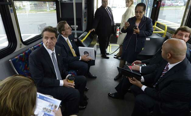 Governor Andrew Cuomo, left  rides a bus with other state officials as he listens to a dialogue by RPI president Shirley Ann Jackson, right during a tour of local businesses as part of a Economic Development Council program.   (Skip Dickstein/Times Union) Photo: SKIP DICKSTEIN / 10019787A