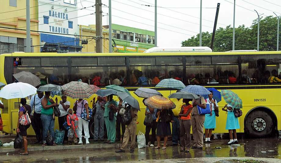 Commuters wait at a bus stop as rain brought by Tropical Storm Sandy falls in Kingston, Jamaica. Forecasters predict the storm will reach Jamaica on Wednesday, most likely as a hurricane. Photo: Collin Reid, Associated Press