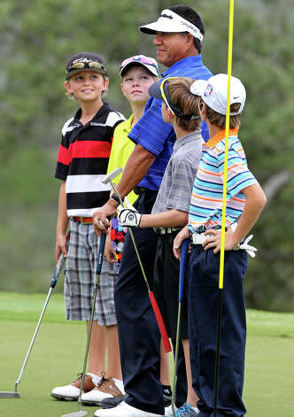 Esteban Toledo gathers his golf mates and instructs on the pose as golfers practice for the AT&T Championship  on October 23, 2012. Boys from the right are Jacob Borow, Zakary Jones, William Moll and Jason Bryant. Photo: Tom Reel, San Antonio Express-News / ©2012 San Antono Express-News