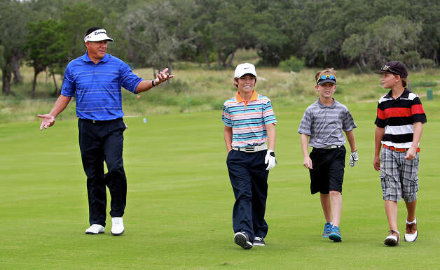Esteban Toledo keeps his partners entertained as golfers practice for the AT&T Championship  on October 23, 2012.  Boys from left are Jason Bryant, William Moll and Jacob Borow. Photo: Tom Reel, San Antonio Express-News / ©2012 San Antono Express-News