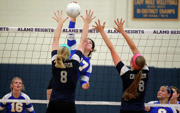 The Lady Mules' Jackie Cabello gets up over the Chargers' Claire Kreuz and Kelsey Lemmons (18) as Boerne Champion beats Alamo Heights 3-0 in volleyball at the Alamo Heights gym on Tuesday, Oct. 23, 2012. Photo: Tom Reel,  San Antonio Express-News / ©2012 San Antono Express-News