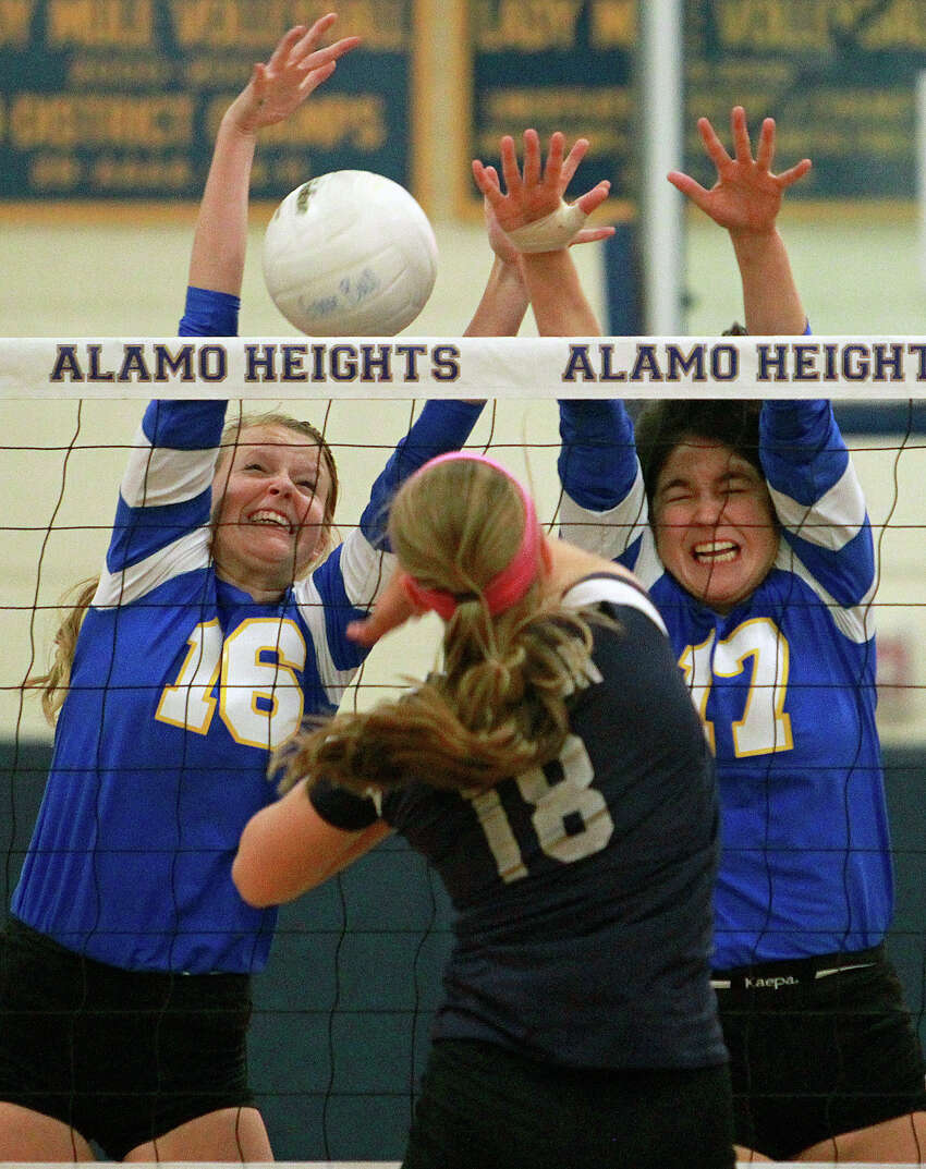 The Lady Mules' Kelsey Mantz (16) and Jackie Cabello fight on the net against a shot by the Chargers' Kelsey Lemmons as Boerne Champion beats Alamo Heights 3-0 in volleyball at the Alamo Heights gym on Tuesday, Oct. 23, 2012.