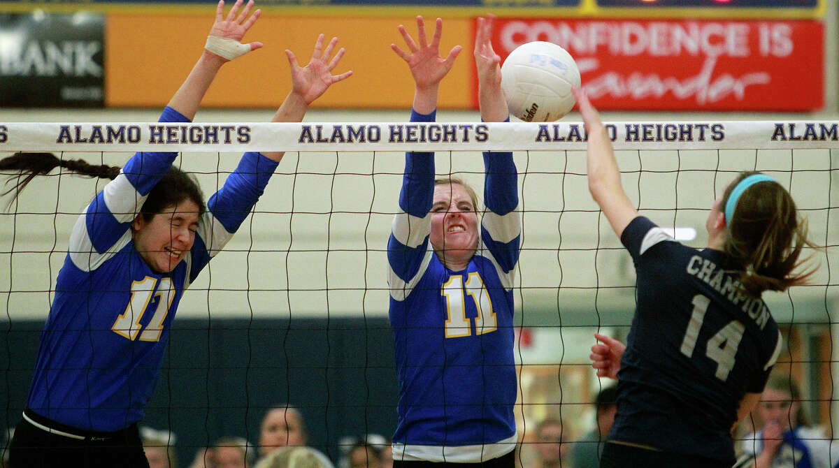 The Lady Mules' Jackie Cabello and Lauren Brockwell (11) defend on the net against the Chargers' Emily Johnson as Boerne Champion beats Alamo Heights 3-0 in volleyball at the Alamo Heights gym on Tuesday, Oct. 23, 2012.
