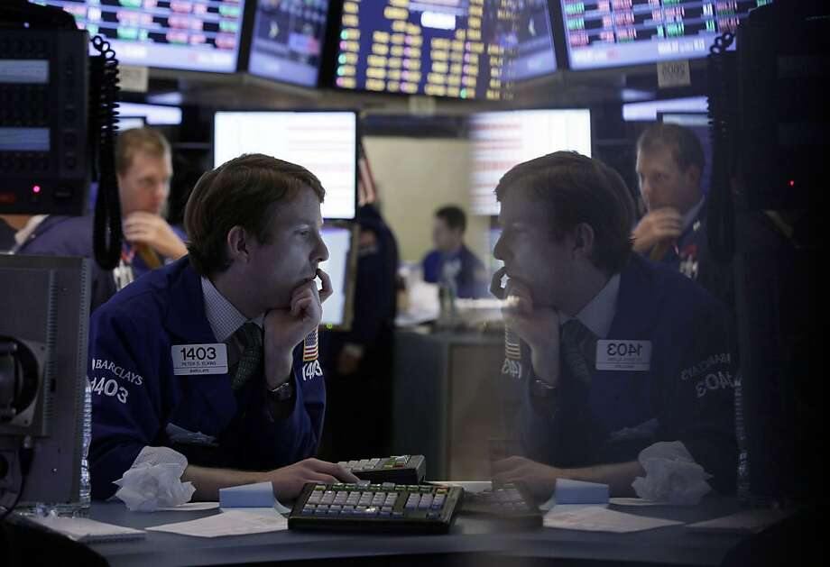 Specialist Peter Elkins, foreground, is reflected in a trading post monitor as he works on the floor of the New York Stock Exchange Tuesday, Oct. 23, 2012. Stocks plunged, making it one of the worst days on Wall Street so far this year and sending the major indexes to their lowest levels since early September. (AP Photo/Richard Drew) Photo: Richard Drew, Associated Press