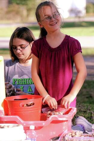 Kassady Thomson and Lauran Edington, both 9 years old, have been working daily in Thomson's fron yard to collect, bag, and sell pecans to benefit their kindergarten teacher, Christina Puente, and her husband, Jesus Puente, who was diagnosed with lymphoma in May.  Puentes daughters and Thomsons brother help the girls on Tuesday, October 23, 2012 in Groves. Photo taken: Randy Edwards/The Enterprise Photo: Randy Edwards