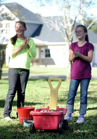 Kassady Thomson and Lauran Edington, both 9 years old, have been working daily in Thomson's fron yard to collect, bag, and sell pecans to benefit their kindergarten teacher, Christina Puente, and her husband, Jesus Puente, who was diagnosed with lymphoma in May.   Photo taken: Randy Edwards/The Enterprise Photo: Randy Edwards