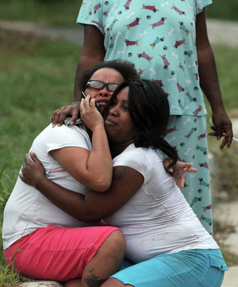 """Women grieve at a crime scene at 4438 N. Hein at the Brighton Terrace apartments Wednesday October 24, 2012. Sergeant Daniel Gonzales said a call came to police as a shooting in progress about 6:30 a.m. . Gonzales said the woman knocked on a door at the apartments saying she had been shot. The woman was pronounced dead at the scene with a gunshot to the torso. """"We have very few leads,"""" Gonzales said. Photo: JOHN DAVENPORT, San Antonio Express-News / San Antonio Express-News"""