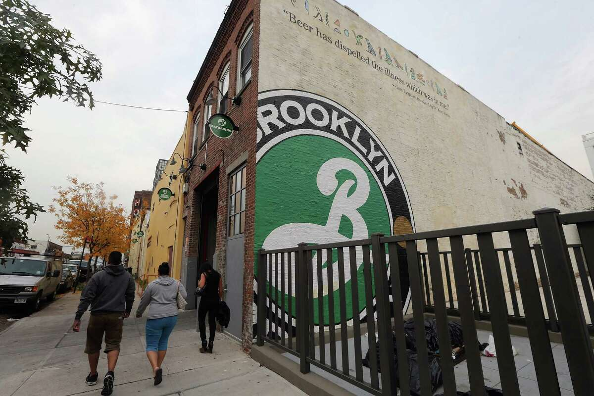 NEW YORK, NY - OCTOBER 23: People walk past Brooklyn Brewery on October 23, 2012 in the Brooklyn borough of New York City. A total of nine fermenters are being installed this week which will allow the craft brewery to make 100,000 barrels of beer per year, 24 hours a day. A mid-year report by the Brewer's Association cited a 12 percent increase in craft beer sales to 6 million barrels this year. The number of American breweries have surged to a 125-year-high of 2,126 breweries last year, 97 percent of which are independent craft breweries. During the pre-Prohibition era Brooklyn had more than 45 breweries and was one of the largest brewing centers in the U.S., today Brooklyn Brewery is the only brewery in the borough.