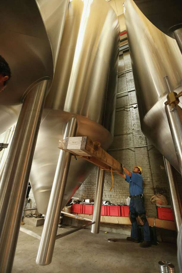 NEW YORK, NY - OCTOBER 23:  A worker helps install a 25-foot tall fermenter at Brooklyn Brewery on October 23, 2012 in the Brooklyn borough of New York City. A total of eight fermenters are being installed this week which will allow the craft brewery to make 100,000 barrels of beer per year, 24 hours a day. A mid-year report by the Brewer's Association cited a 12 percent increase in craft beer sales to 6 million barrels this year. The number of American breweries have surged to a 125-year-high of 2,126 breweries last year, 97 percent of which are independent craft breweries.  During the pre-Prohibition era Brooklyn had more than 45 breweries and was one of the largest brewing centers in the U.S., today Brooklyn Brewery is the only brewery in the borough. Photo: Mario Tama, Getty Images / 2012 Getty Images