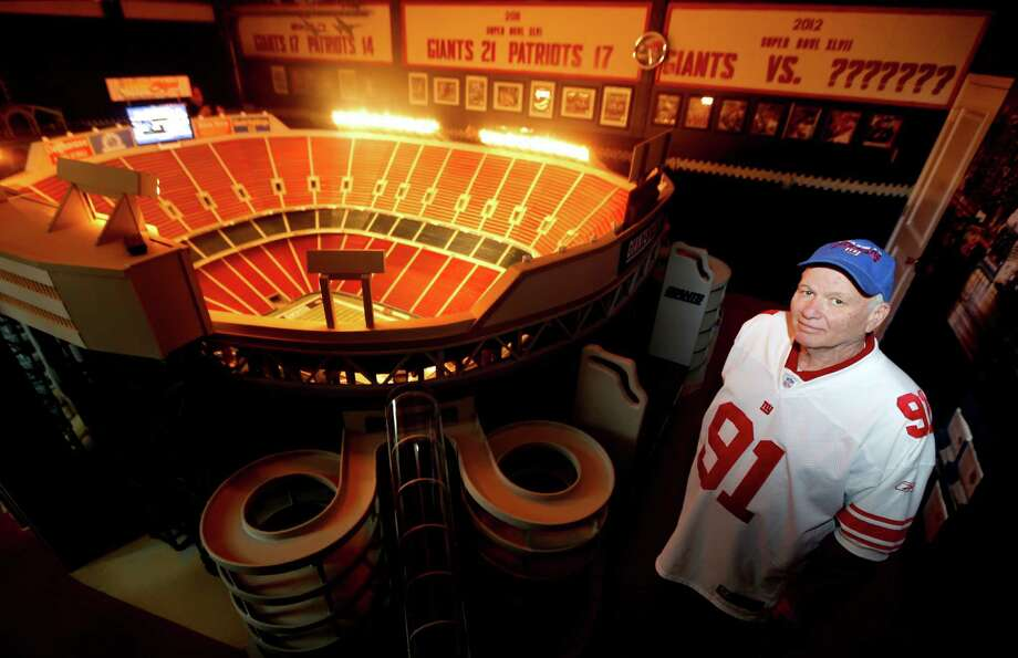 Don Martini poses for photos next to his miniature replica of Giants Stadium, the former home of the New York Football Giants, Tuesday, Oct. 23, 2012, in Blairstown, N.J. According to Martini, the replica took him two years to build and is pretty close to what the actual stadium looked like before it was demolished. The stadium features its own lighting equipment and two television monitors serving as stadium scoreboards. Photo: Julio Cortez, AP / AP