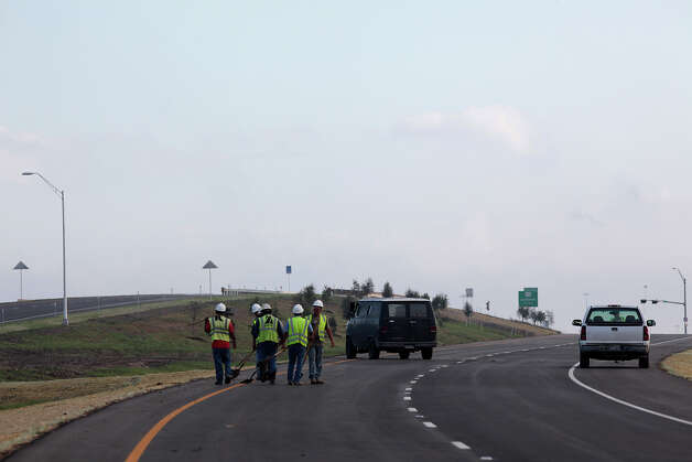 Crews prepare for the opening of Texas 130 just west of Lockhart, Texas, Wednesday, Oct. 24, 2012. The toll road which runs from IH-10 just east of Seguin, will connect with Texas 45, a toll road that circumvents Austin. Motorist will be able to drive 85-miles-per hour on Texas 130. A ribbon cutting ceremony is on scheduled for Wednesday morning with Gov. Rick Perry doing the honors. Photo: Jerry Lara, San Antonio Express-News / © 2012 San Antonio Express-News