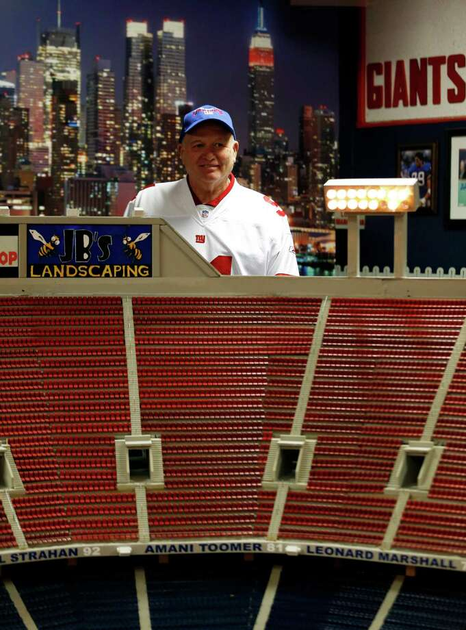 Don Martini poses next to his miniature replica of Giants Stadium, the former home of the New York Football Giants, Tuesday, Oct. 23, 2012, in his garage in Blairstown, N.J. According to Martini, the replica took him two years to build and is pretty close to what the actual stadium looked like before it was demolished. Photo: Julio Cortez, AP / AP