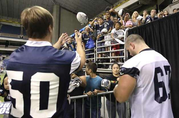 Fans toss a football to linebacker Sean Lee (50) as guard/center Phil Costa signs an autograph after the morning practice session of the Dallas Cowboys training camp at the Alamodome on Wednesday, July 28, 2010. Kin Man Hui/kmhui@express-news.net Photo: KIN MAN HUI, SAN ANTONIO EXPRESS-NEWS / San Antonio Express-News
