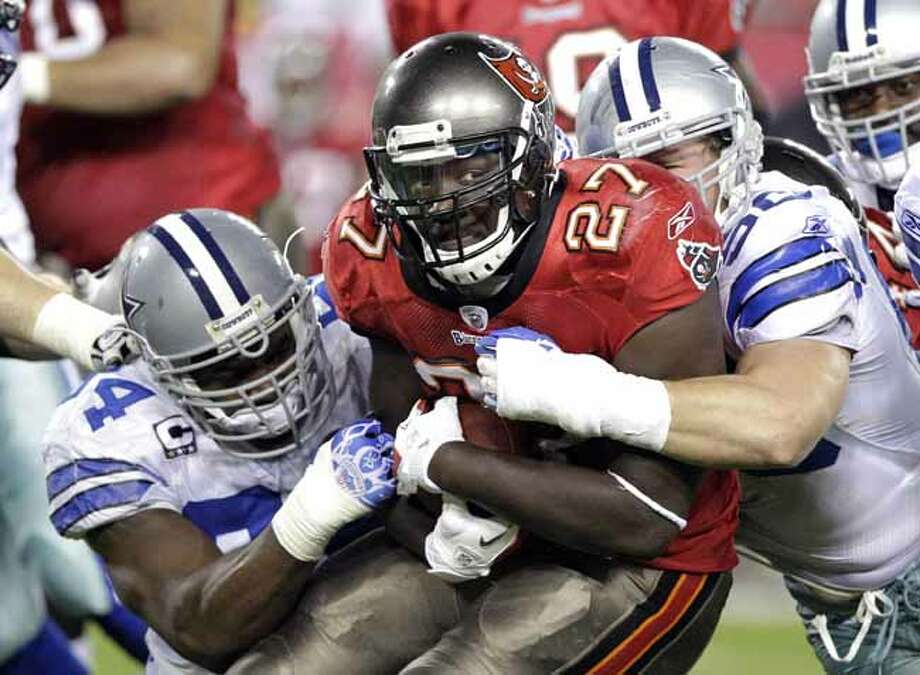 Tampa Bay Buccaneers running back LeGarrette Blount (27) is stopped after a short gain by Dallas Cowboys outside linebacker DeMarcus Ware, left, and inside linebacker Sean Lee during the first half of an NFL football game on Saturday, Dec. 17, 2011, in Tampa, Fla. (AP Photo/John Raoux) Photo: John Raoux, Associated Press / AP