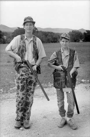 William, left, and brother Maverick Fisher were kitted out in camo to hunt at the family's Piquines Ranch in Tarpley, Texas in 1987.