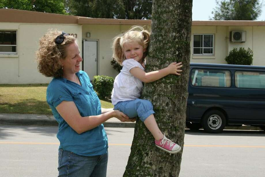 "I was stationed at Kadena AB, Okinawa, Japan 1978 - 1981 when my wife Betty Jean helped our 3-year-old daughter Theresa to ""climb"" the palm tree in front of our base quarters. Theresa visited friends at Kadena in early 2011 and took this photo helping her daughter Kate ""climb"" the same palm tree 30 years later.