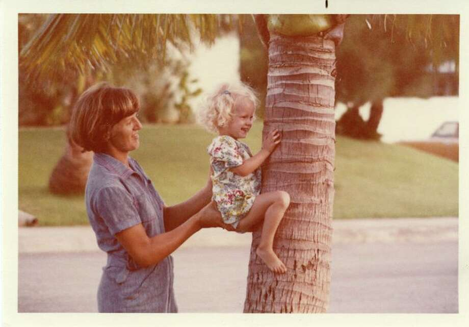 """I was stationed at Kadena AB, Okinawa, Japan from 1978 to '81 when my wife Betty Jean took this photo helping our 3-year-old daughter Theresa """"climb"""" a palm tree in front of our base quarters.   --Pete Siegel Photo: Pete Siegel, Reader Submission"""