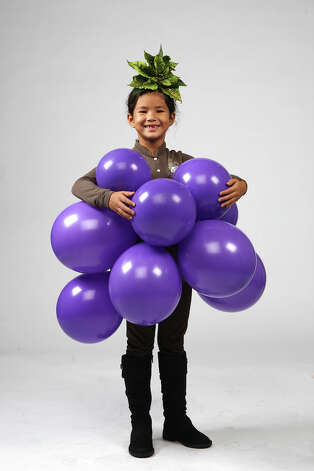 Purple balloons and faux leaves turn Lulu McCutchen into a walking bunch of grapes. Photo: Jerry Lara, San Antonio Express-News / © 2012 San Antonio Express-News